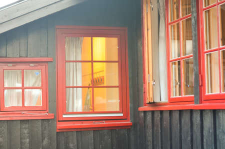 upper floor: view through red window into a lighted house
