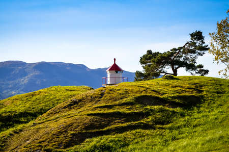 small lighthouse at norwegian fjord in autumn