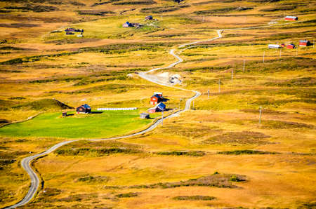 long and winding road with red houses during autumn in norway