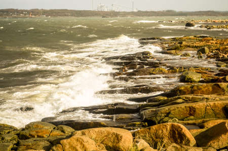 waves crashing at rocky shore in swedish landscape in autumn Stock Photo