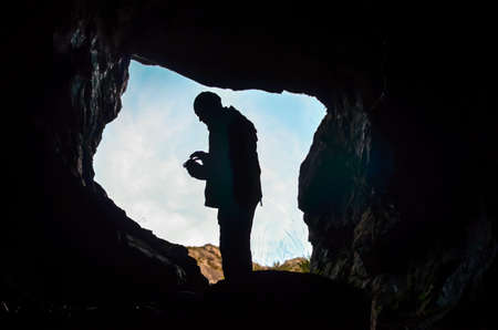 dark cave: dark cave with man silhouette and water