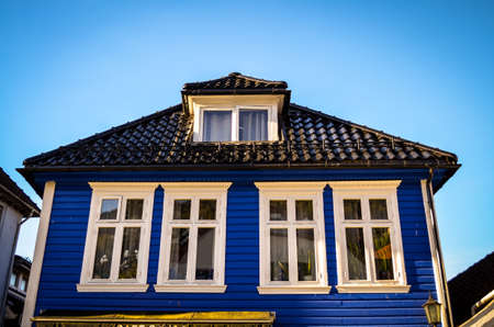 residential idyll: blue wooden house with white frames in bergen, norway