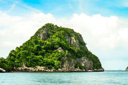 aonang: Lone green island in clear tropical sea