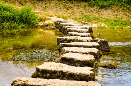 stepping: stepping stones crossing a small river in summertime