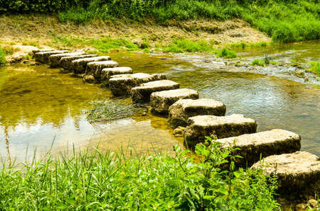 stepping stones crossing a small river in summertime