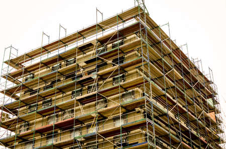bare brickwork of a building with scaffold