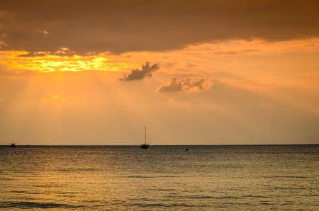 puesta de sol con rayos de sol y barcos en la playa tropical