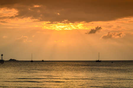sunset with sunbeams and boats at tropical beach Stock Photo