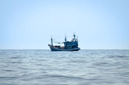 blue Fishing trawler on the ocean water alone