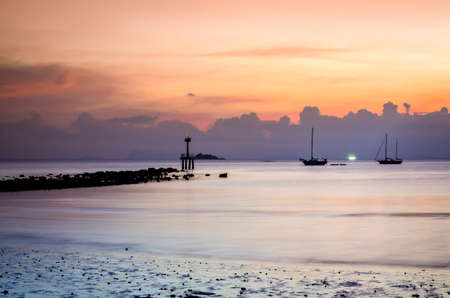dramatic sunset at tropical beach with boat silhouettes