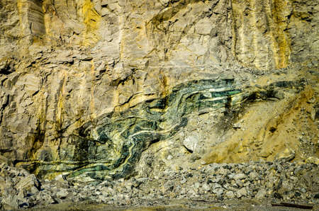 ductile: green folded rock formation inside mountain wall