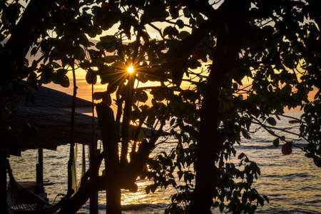 tropical sunset with sunbeams and hammock at the beach Stock Photo