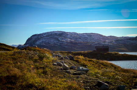lonely wooden house in rough norwegian landscape
