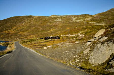 countryroad in autumnal highland tundra landscape, norway