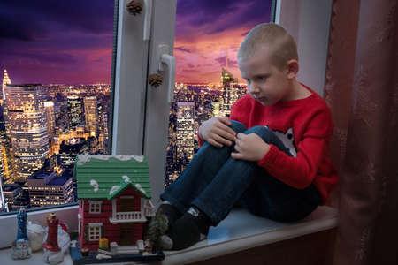 windowsill: The photo depicts a boy on a windowsill