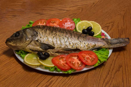 fish plate: The photo shows a fish on a plate with tomatoes and olives Stock Photo