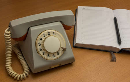 landline phone: The photo depicts a landline phone with a notebook