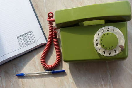 depicts: The photo depicts a landline phone with a notebook