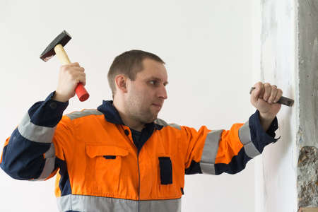 chisel: The photo depicts a man with a chisel and hammer Stock Photo
