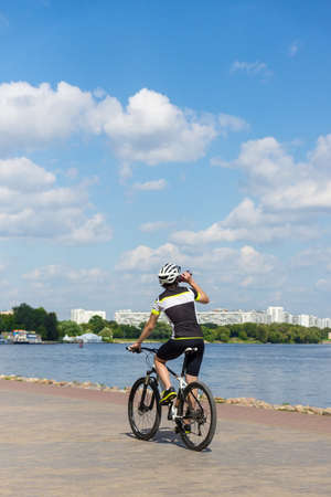 depicts: The photo depicts a cyclist racing along the river