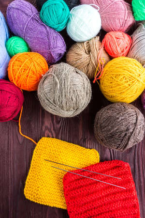 knitting ball of yarn and knitting needles on a red background