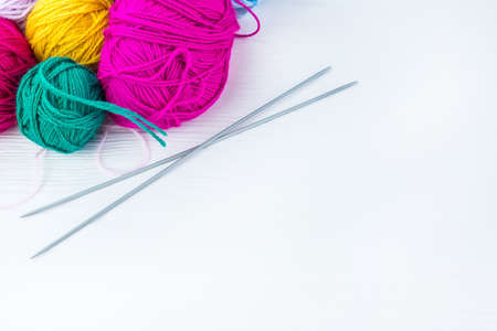 knitting ball of yarn and knitting needles on a white background
