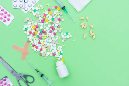Assorted pharmaceutical medicine pills, tablets and capsules over green background Stock Photo