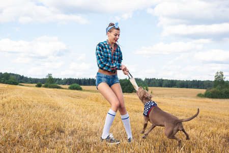 girl who trains dog breed pit bull in nature Foto de archivo