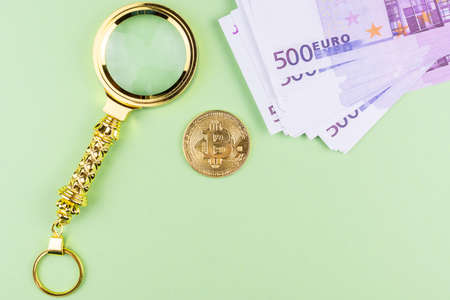 bitcoin increased the magnifying glass next to the Euro banknotes on a green background, hand holds a magnifying glass over bitcoin