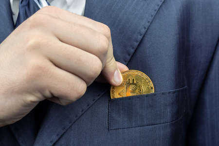 Businessman removing or placing a golden bitcoin in a pocket of his suit jacket in a wide close up view Imagens
