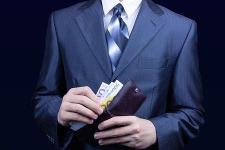 Der Mann im Anzug entfernt das Geld aus dem Portemonnaie, das Businessman Portemonnaie Euro