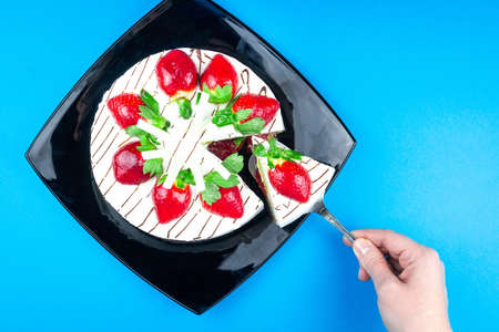 Strawberry cake with white chocolate on a black plate blue background, Cream strawberry cake
