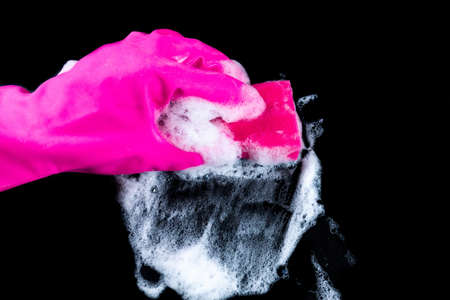 A gloved hand wipes foam and dirt with a washcloth. Cleaning Stock Photo
