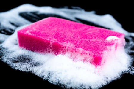 Cleaning sponge with foam for dish washing on black background