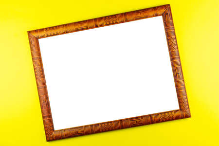Wooden frame isolated on a yellow background Stock Photo