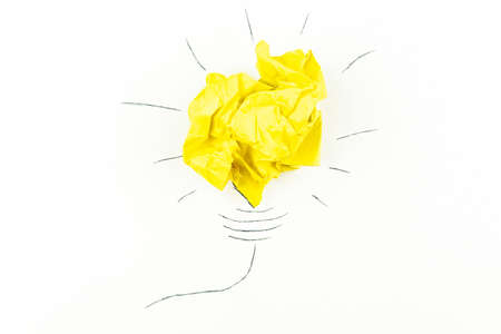 creative concept idea, a new idea. Painted light bulb with a crumpled paper yellow ball.