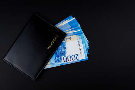 Russian passport with money inside on a black background