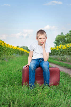 Sad lonely boy sitting on the road in a field of sunflowers on a suitcase and waiting for transport