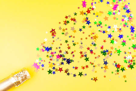 Champagne bottle with colorful sprinkles on yellow background