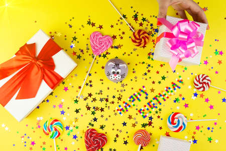 Happy birthday concept with copy space, cake, gifts and caramel for birthday on yellow background