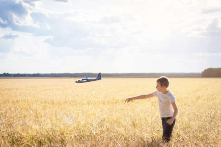 Child playing with airplane toy, boy imagines discovery adventure, blue sky background Фото со стока