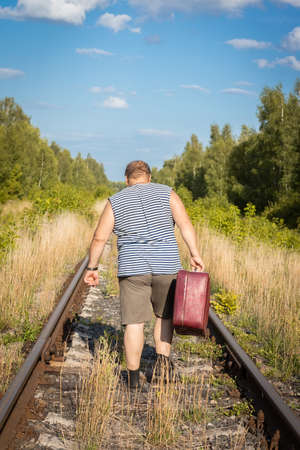 a man with a suitcase goes by rail