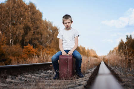 boy child  sitting on a suitcase on the railway waiting for the train