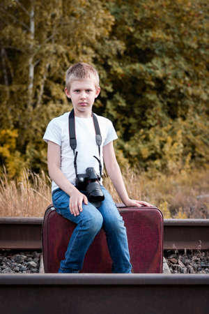 Boy with a camera on the railway in nature