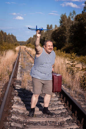 a man with a suitcase goes by rail and launches a toy plane into the sky Stock fotó