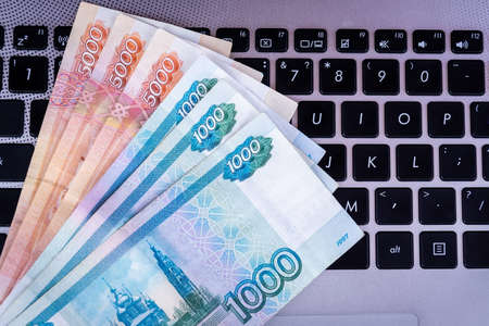 A pack of Russian rubles lies on the laptop keyboard. Top view. Stock fotó