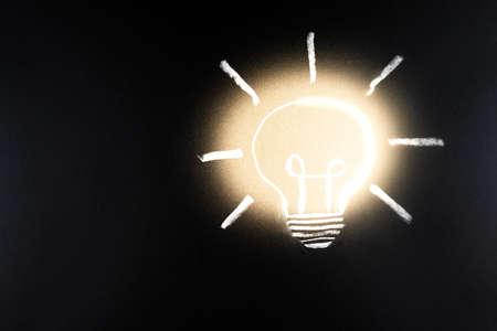 Lightbulb drawn in chalk on blackboard drawing light Bulb on black background