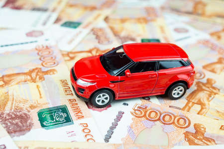 The red car is on the money, a Toy car on money