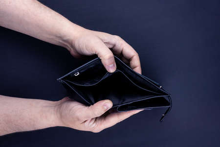 men's hands hold an empty purse. A wallet with little money in it. The concept of poverty and bankruptcy 写真素材