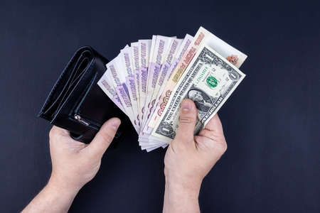 A man is holding an open wallet with money in his hands. Hands take out bills from his wallet. The concept of rejection of paper money, inflation, financial crisis.